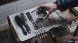 High angle view of barbershop tools on the shelve and male hands taking straight razor and placing bowl with shaving cream and brush in it