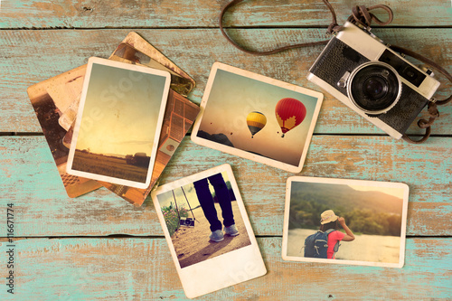 Fototapeta Photo album remembrance and nostalgia in summer journey trip on wood table. instant photo of vintage camera - vintage and retro style