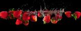 Strawberries splashing into water on a black background - 116674914