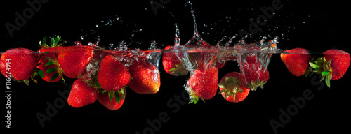 Strawberries splashing into water on a black background - 116674914
