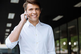 Cheerful young businessman talking by cell phone on the street