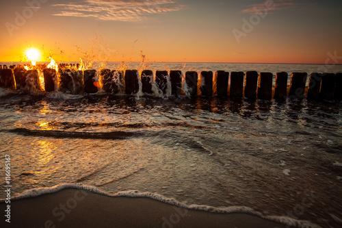 Zdjęcia na płótnie, fototapety na wymiar, obrazy na ścianę : Sunset at Baltic sea, view on old breakwater piles.