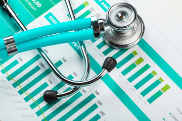 Stethoscope with financial on the desk.