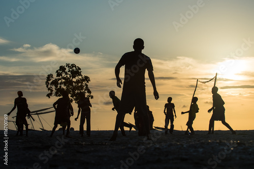 Deurstickers Zanzibar Men playing football on the beach at sunset
