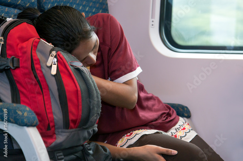 Poster woman with a backpack sleeping in a train