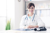 Doctor working at office desk - 116743793