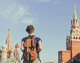 Young attractive woman traveler with backpack on the background