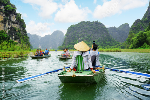 Poster Tourists in boats. Rowers using feet to propel oars, Vietnam