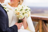closeup of bride hands holding beautiful winter wedding bouquet