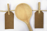 White background with sisal rope and clothes pins with empty copy space tags wooden ladl spoon