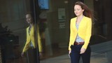 Focus on the reflection. Slow motion. Young business woman in yellow jacket walking near office building in the big city.