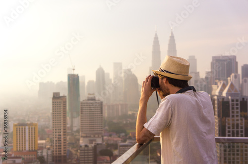 Poster Tourist taking pictures of skyscrapers at sunrise