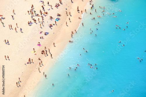 Tourists on the sand beach of Navagio Zakynthos Greece. People b