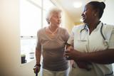 Nurse assisting senior female patient to walk