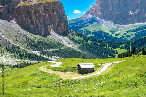 Single house on the green field that surrounded by mountain at Dolomites, Italy