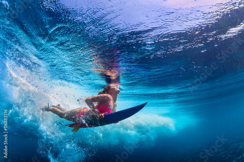 Fototapeta Young active girl wearing bikini in action - surfer with surf board dive underwater under big ocean wave. Family lifestyle, people water sport adventure camp and beach extreme swim on summer vacation.
