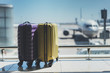Leinwanddruck Bild - Two suitcases in the airport departure lounge, airplane in the blurred background, summer vacation concept, traveler suitcases in airport terminal waiting area
