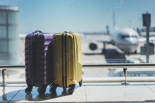 Leinwanddruck Bild Two suitcases in the airport departure lounge, airplane in the blurred background, summer vacation concept, traveler suitcases in airport terminal waiting area