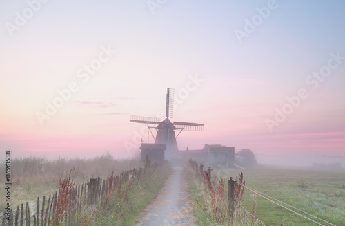 Dutch windmill in dense morning fog - 116961538