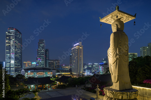 Mireuk Daebul statue (The Great Statue of Maitreya Buddha) at the Bongeunsa Temple and view of Gangnam in Seoul, South Korea at night Poster