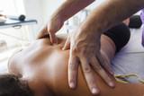 Fototapety Fisioterapeuta trabajando los hombros de una joven deportista. Quiromasajista terapéutico trabajando. Tratamiento de sobrecarga muscular.