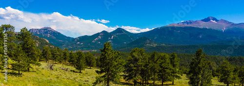 view of  the  meadows and foot hills  below the snow dotted  peaks of the Rocky Mountains in Colorado