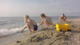 4K Children Playing On Seashore, Summer View. The boy ran away from sea waves.