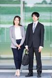 自動ドアの前に立つ男女(ビジネス・共働き・夫婦・同僚)