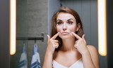 Woman checking wrinkles on face in front of bathroom mirror - 116997340
