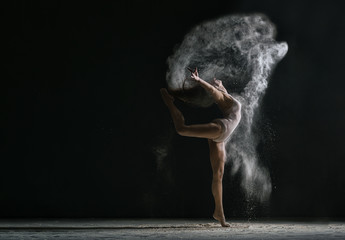 Concept. Flexible girl dancing in cloud of dust