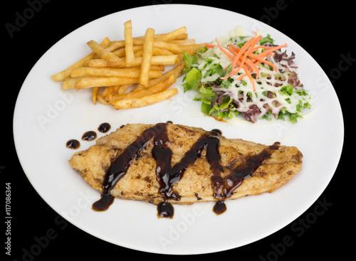Poster Fish fillet with french fries and salad isolated on the black background with cl