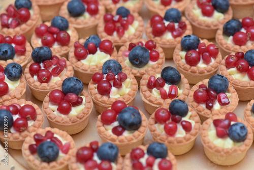 Fototapeta Mini tarts with vanilla cream, blueberries and redcurrants