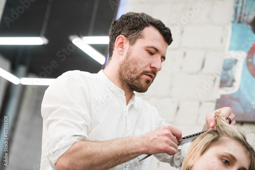 Hairdresser cutting client's hair in salon with electric razor closeup Poster