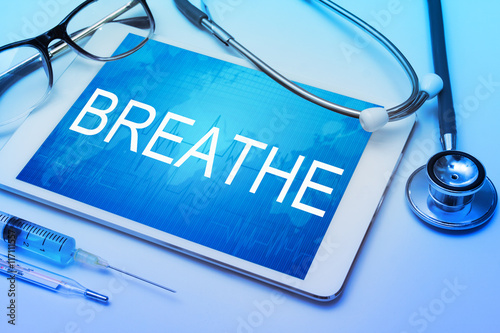 Poster Breathe word on tablet screen with medical equipment on background