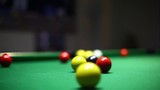 Color footage of some balls on a green table during a billiards match.