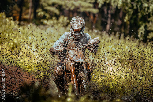 mata magnetyczna extreme motocross competition: athlete racer goes through a puddle of mud