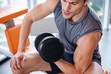 Man athlete sitting and exercising with dumbbell in gym