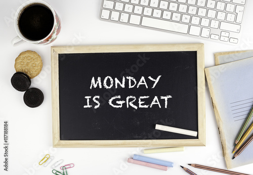 Chalkboard on office desk with text: Monday is a great