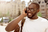 Joyful smiling man talking on cell phone