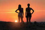 Beautiful landscape with silhouette of young sporty girls in the evening on the hill in summer. Colorful sunset sky. Fitness women resting after sport, workout, run.