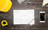 Designer work on website idea. Work desk with smart phone, glasses, paper, pencil, construction tools.