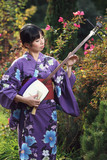 Beautiful woman with kimono playing shamisen