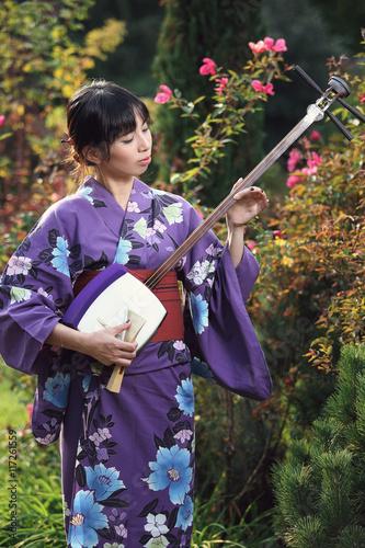 Beautiful woman with kimono playing shamisen Poster