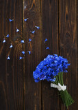 Bouquet of cornflowers with petals lying on a dark wooden table.