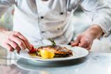 Koch mit Sorgfalt beim Garnieren eines Gerichts, Fisch mit Gemüse - 117285377