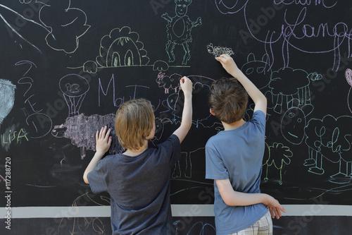 Fotobehang Overige enfants dessinant sur un grand tableau noir