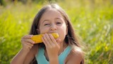 Little girl eating a boiled corn outdoors on a sunny day.
