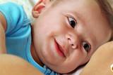 retrato de un hermoso bebe feliz sonriendo con su madre en la cama.