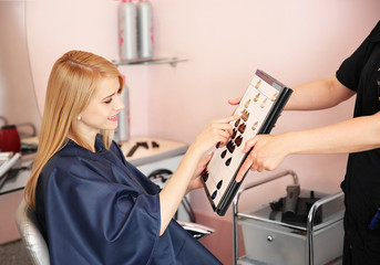 Young blond woman choosing from hair color palette
