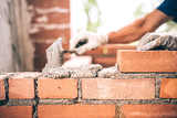 Bricklayer worker installing brick masonry on exterior wall with trowel putty knife - 117356924